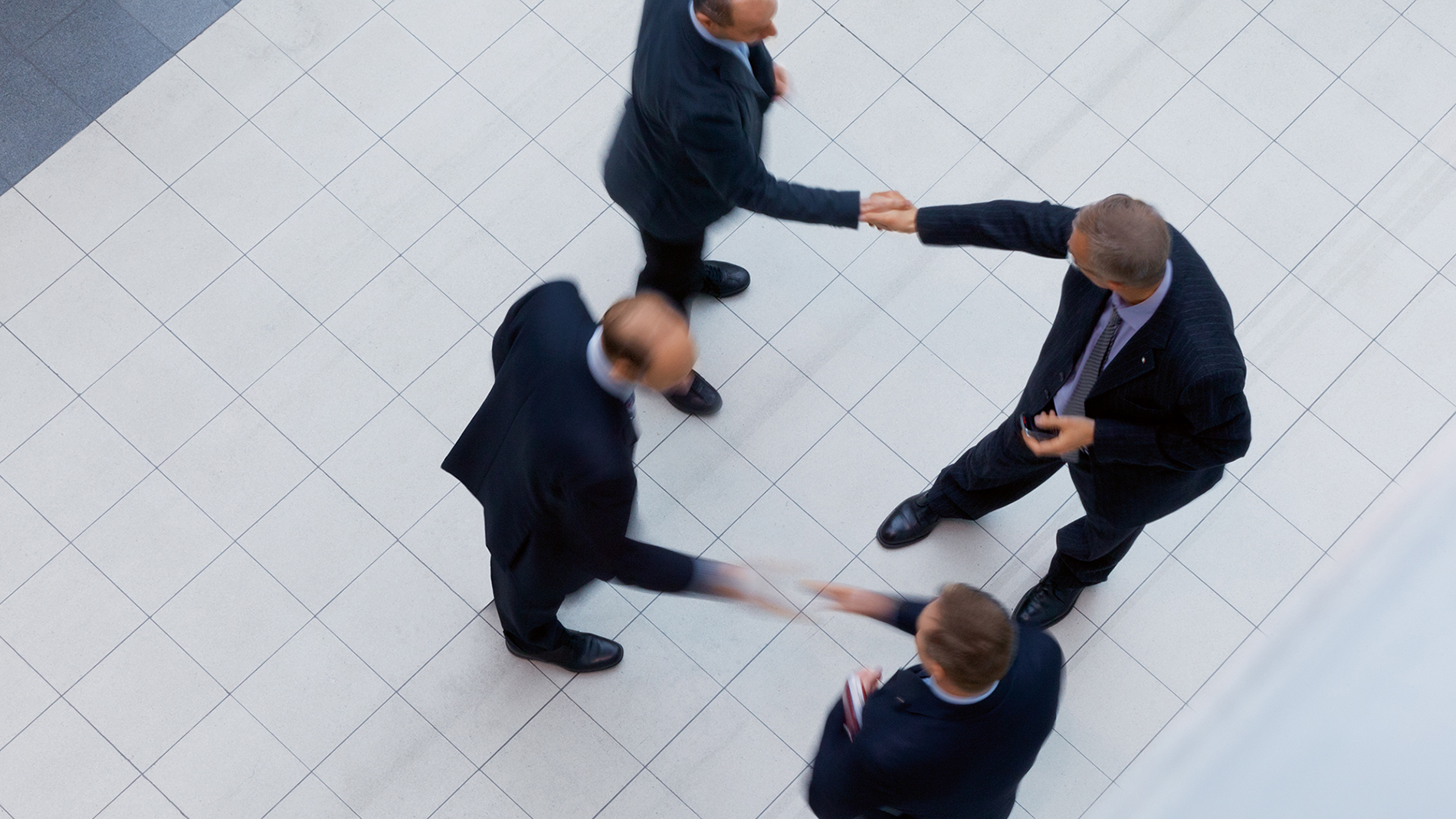 4 businessmen greet each other with hand shakes